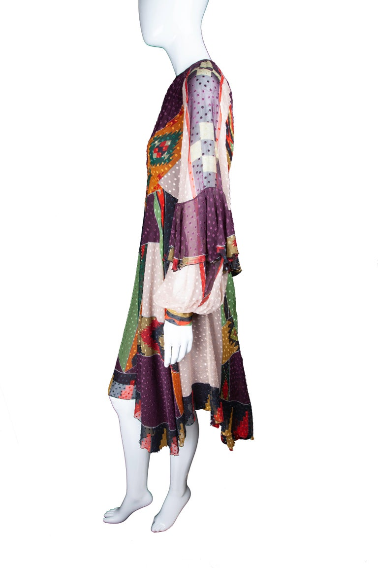 This Fall 2018 Runway Etro dress features long, balloon sleeves, a Native American inspired multicolor print, a fitted waist, flare skirt, and midi length. The dress also includes a sash that can be tied around the waist or worn as a scarf. Brand
