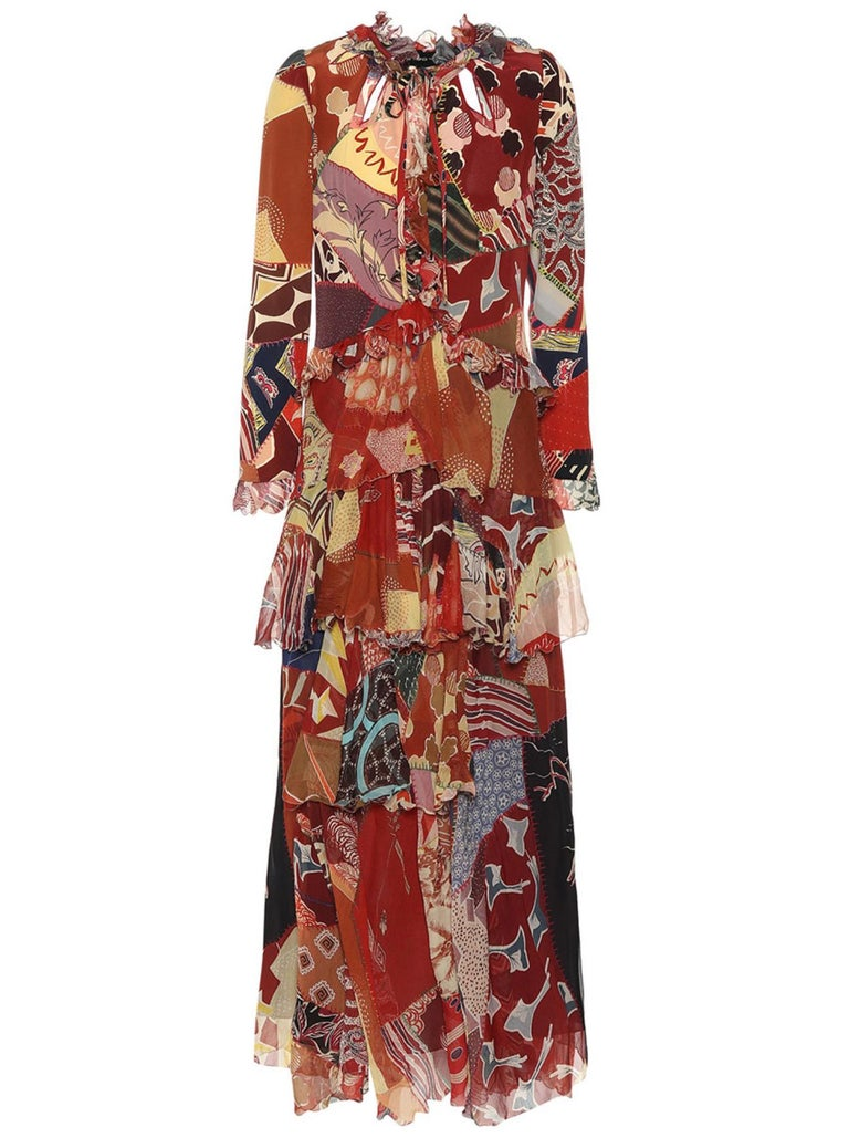 This Fall 2018 Runway Etro maxi dress features silk crêpe and crinkled chiffon material, a ruffled tiered silhouette, long sleeves, cutout details that are embroidered with red edges along the v-neck line, and a bold, colorful print. Brand new with