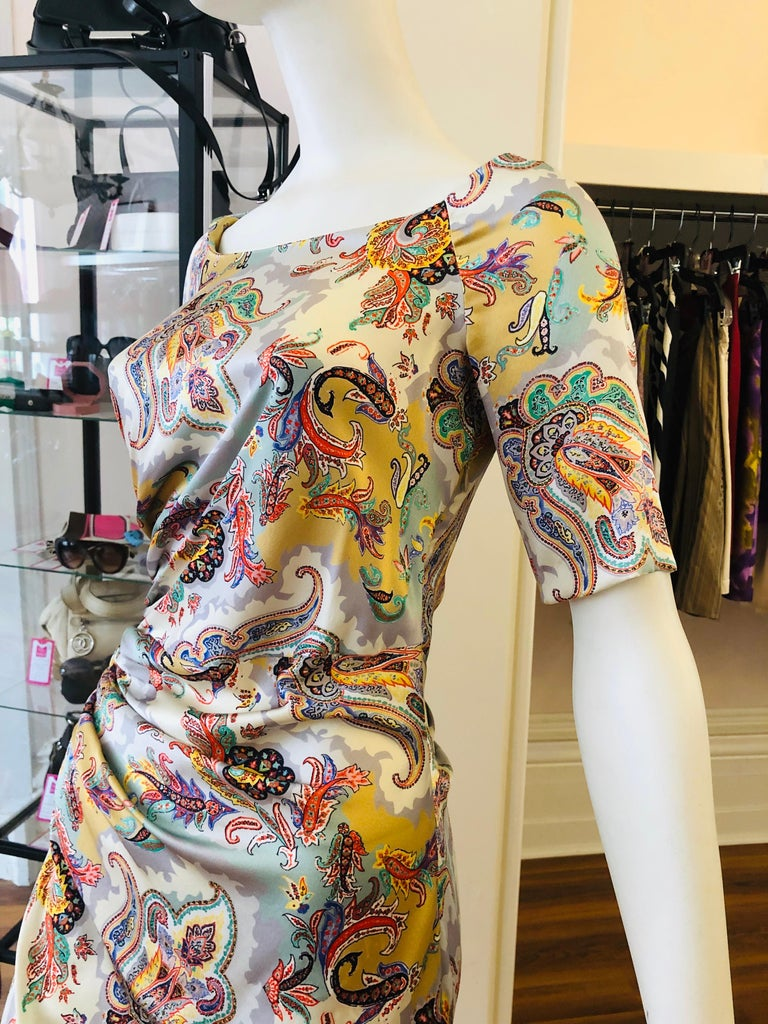 ETRO silk dress with 7% elasthane which give it some stretch. There is side draping on both the front and back and the colors go from silver to green, orange and gold. This dress is very versatile as it can be worn from day to night. There is an