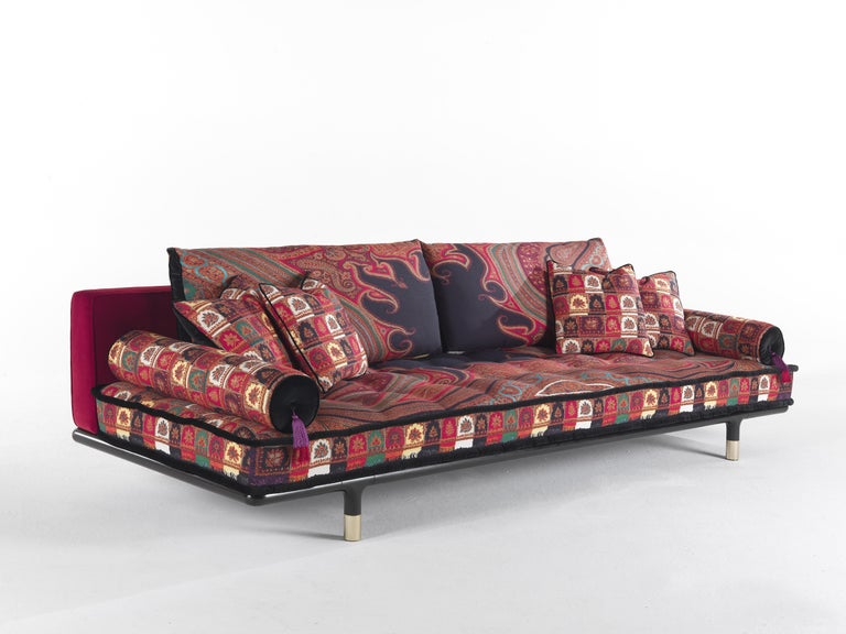 A sofa with a welcoming and comfortable look, emphasized by the mattress conformation of the seat. Refined details such as the polished brass tips of the basement and the roll cushions with decorative tassels enhance the whole effect, showing the