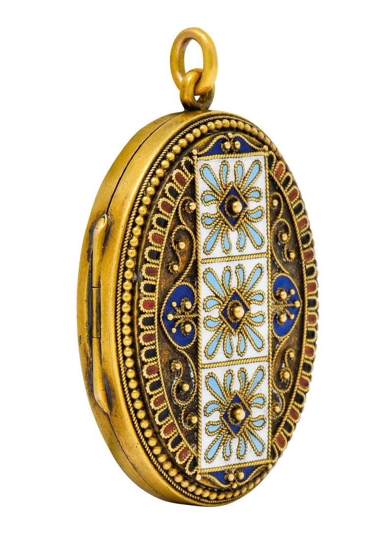 Substantial oval locket decorated to front with scrolled twisted rope motif and gold beading  Depicting three squares with floral decoration surrounded by a scalloped border  Accented throughout by white, blue, red, and black enamel; exhibiting very