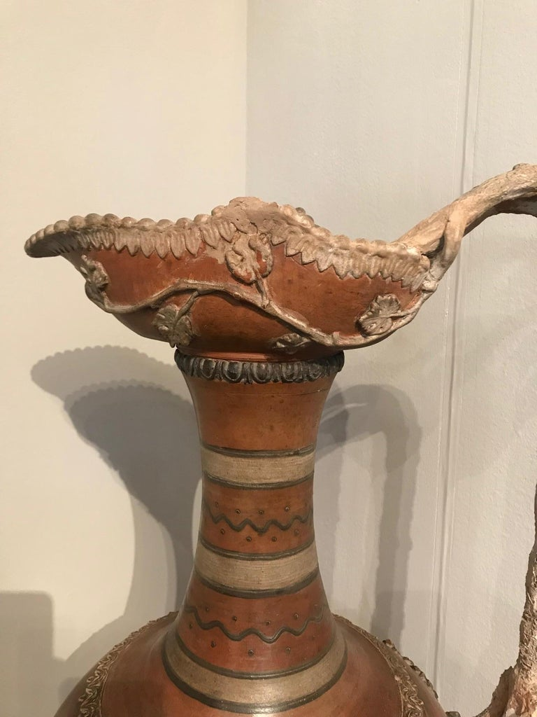 Etruscan style terracotta ewer with wine leaf motifs.