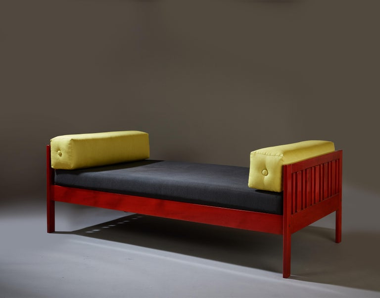 Ettore Sottsass (1917-2007)   A lively and playful modernist daybed or sofa by Memphis Milano founder Ettore Sottsass, in red lacquered walnut with a black-upholstered cushion and two bolster pillows in chartreuse.   An early work by the
