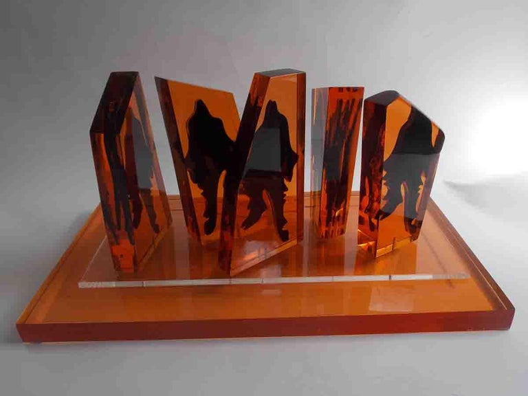 A group of amber monoliths with encased abstract figures.