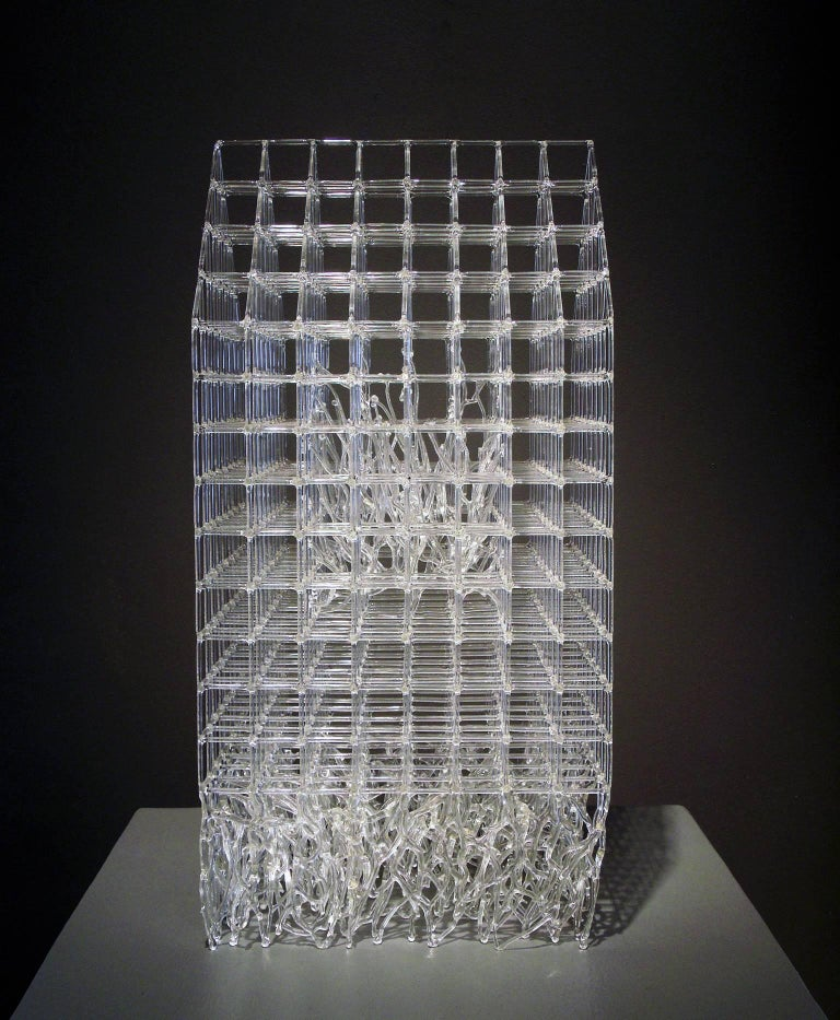 House Barrier VII by Eunsuh Choi is an intricate glass house with root-like tendrils of glass underneath. In the center there is a second house but it is only visible as such from certain angles. This piece is made entirely of flameworked,