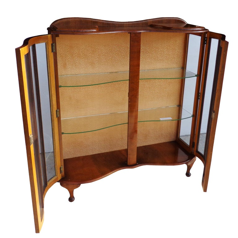 Art Deco walnut glass curio display cabinet  Beautiful concave front with glass display shelves. Queen Anne legs.  Measures: 41? Width x 13? Depth x 46.5? Height.