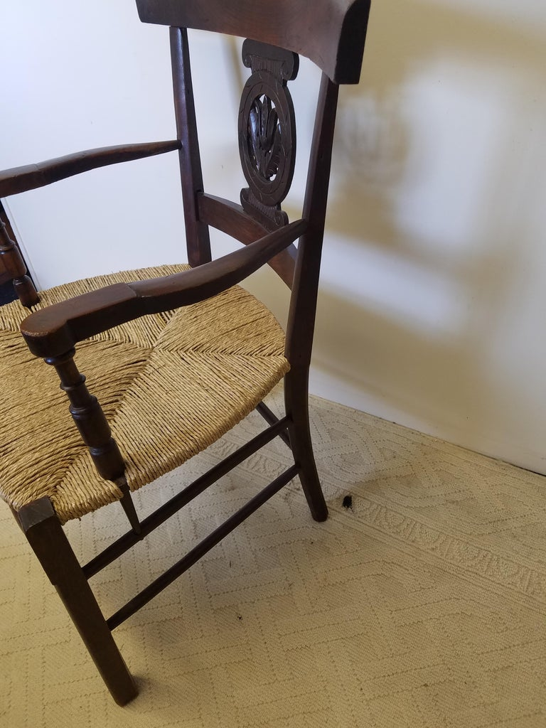 Wonderful European turn of the century oak armchair with carved back splat, shapely arms and curved and turned stretchers. Rush seat replaced at a later date. Very good condition. Measures: 24 W x 23 D x 36 H. Seat height 17.25.
