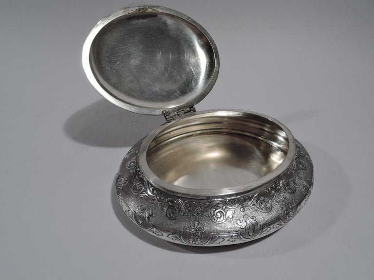 """Turn of the century European 800 silver keepsake box. Oval and bellied. Cover hinged and domed with cast elephant finial. Engraved scrolls, flowers, and leaves on stippled ground. Marked """"800"""". Weight: 13 troy ounces."""