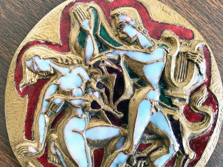 Boldly sculpted in gilded bronze and gorgeously enriched with several shades of enamel, including mother of pearl and ruby red, this midcentury rondel depicts two nude figures Orpheus and Eurydice with a lion rearing between them. Orpheus is