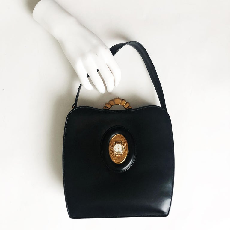 Authentic, preowned, vintage & RARE Evans Elegance black calfskin leather bag w/clock, circa 50s. Comes w/gold mirror compact & attached coin purse. Art Deco metal top closure, hinged, lined in satin w/slit pockets & 1 small open pocket.