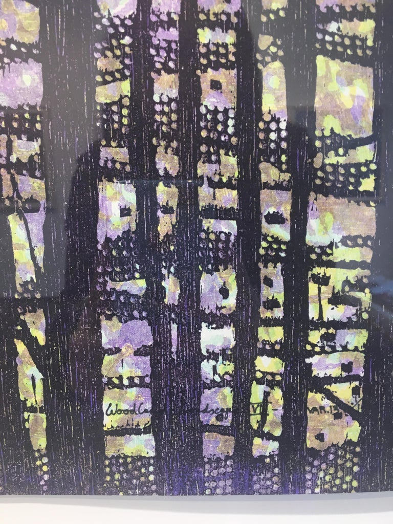 This square woodcut print on paper evokes the peacefulness of looking through a woodland scene. The dark navy blue silhouette of the forest is offset by the pale lavender purple background with hints of light yellow. Price shown is the framed price,