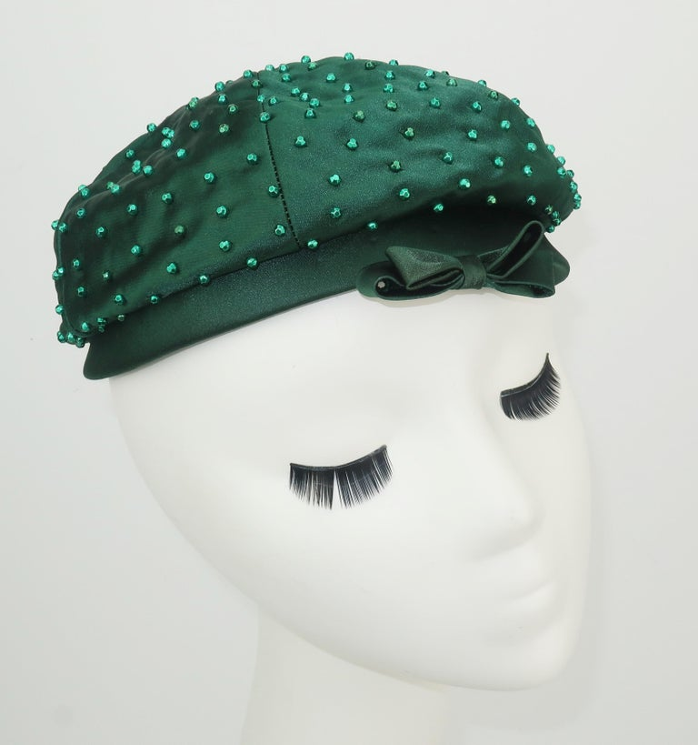 A 1950's Evelyn Varon tam style hat in a rich hunter green satin embellished with faceted beads and a bow.  Perfect for adding glamour to day wear or a topper for evening.  Very good condition ... appears rarely worn. MEASUREMENTS The inside rim