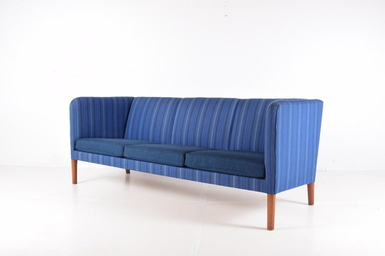 Elegant even arm sofa on tapered teak legs, designed by Hans J. Wegner, circa 1955. This example, produced by the workshop of A.P. Stolen, Denmark, circa 1971. Purchased from original owner who imported it from Copenhagen in 1971. Upholstered in the