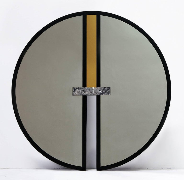 Circle and oval forms unite to create the graphic everything is golden mirror series.   No. 6 is a circular mirror with a glossy black lacquered frame, inset with gold and silver mirrored stainless steel and Grigio Carnico marble.  It also