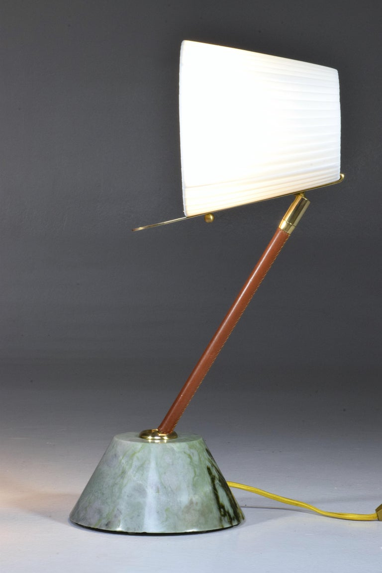 Contemporary handcrafted articulating table lamp designed in a gold polished brass stem adorned with a brown sheathed leather detail hand sewn by artisan saddle makers which articulates at the base with a ball joint . The shade is built with a