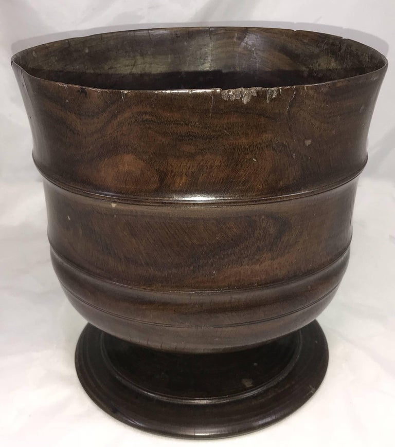 An exceptional example of a carved English Wassail bowl, circa 1680, in figured lignum vitae with incised band decoration on the bowl, supported by a wide carved foot, with great overall patina. The word 'wassail' comes from the Anglo-Saxon phrase