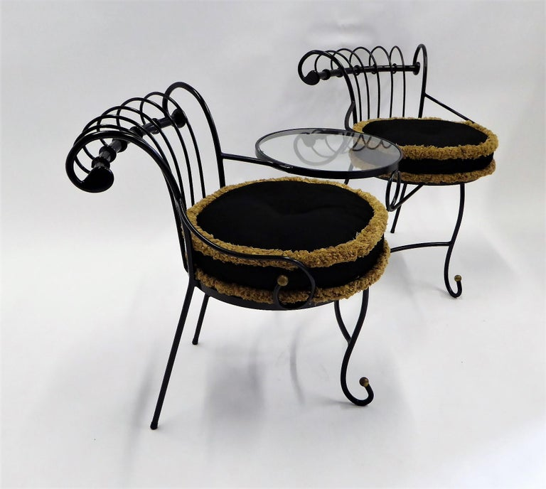 This exceptional wrought iron Tete a Tete or settee is either French or Italian and is heavily influenced by the designs of Maurizio Tempestini for Salterini. Having a small circular glass table between the seats and a curved design on the seatbacks