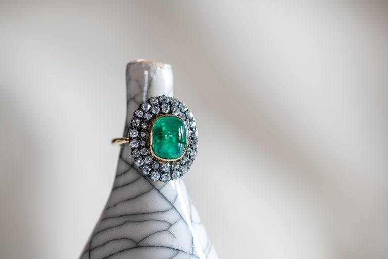 The large cabochon emerald at the centre of this vintage-style ring is bold and bright, its vivid green colour accentuated by a double-layered surround of round brilliant white diamonds. Hand-crafted in the Haruni workshop, this is a dazzling ring