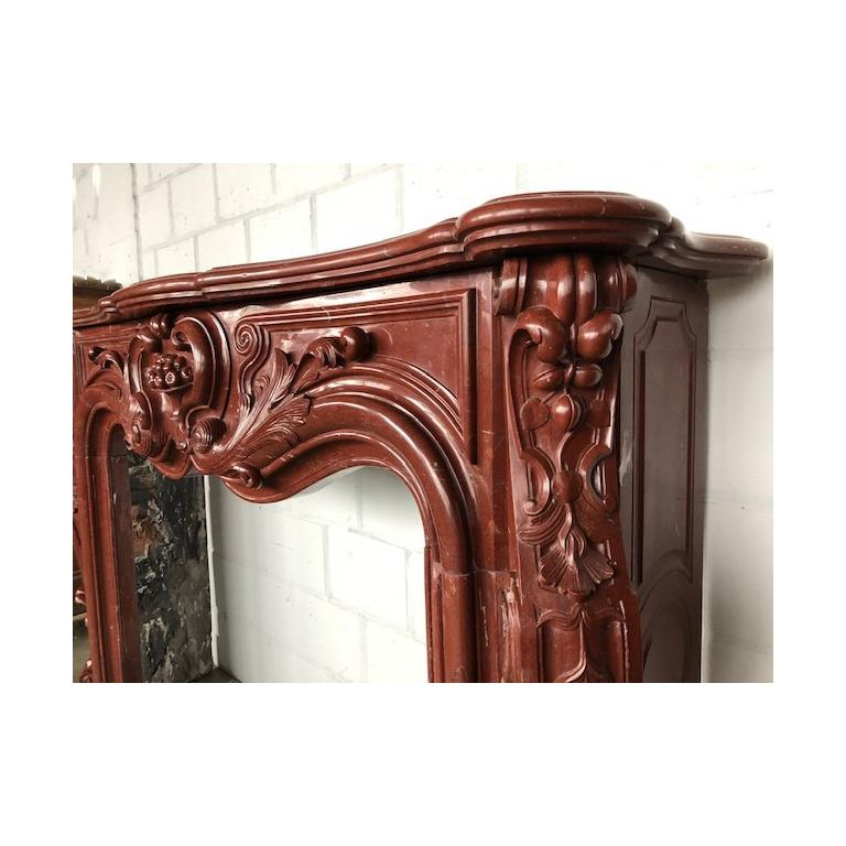 This beautiful, antique Louis XV fireplace was made out of the highly-valued red Griotte marble, during the 18th century. Extremely curved and decorated with flushy sculptures. The center of the frieze is ornated with a vase and fruit. The winding