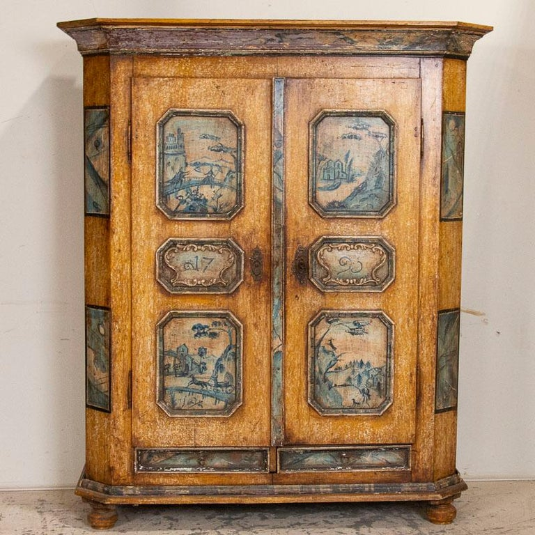 Exceptional in every way, this original painted armoire exhibits superb craftsmanship. Dated 1795, each of the panels exhibits rare hand painted landscape scenes that include a couple on bridge with castle in background, a hunting scene, couple on a