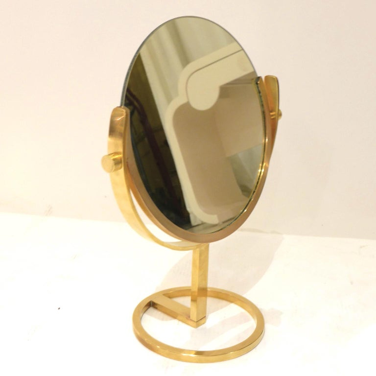 A heavy high quality brass vanity or table mirror with beautiful patina and sleek proportions that would look great on any dresser or vanity.