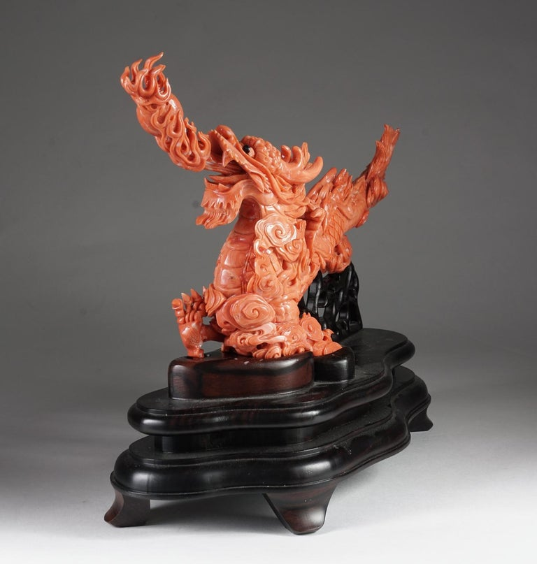 An exceptional Chinese carved coral dragon with fire, Qing dynasty.  Very finely carved. With original wooden base.  Measures: Coral: 7.5
