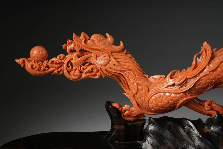 An exceptional Chinese carved coral dragon with fire, Qing dynasty.  Very finely carved. With original wooden base.  Measures: Coral 5