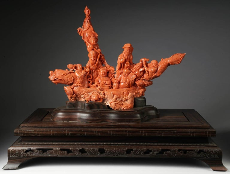 An exceptional Chinese carved coral figural group or statue of a boat with eight immortals. The boat in a form of a carved dragon with fish throughout.