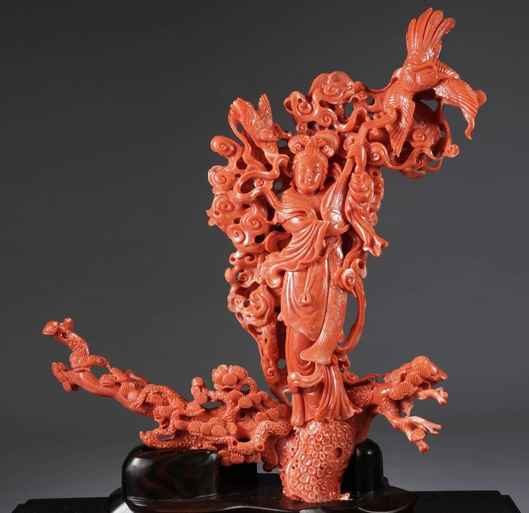 An exceptional Chinese carved coral figural group of a Guanyin, Kwan Yin with a Phoenix.  Very finely carved. In a custom made glass and wooden museum case. The coral has a nice, deep-red color.  Coral measures: 13