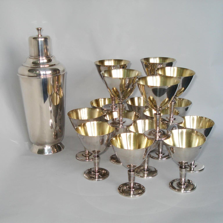 An Art Deco Shaker accompanied by 16 cocktail glasses, martini goblets, making a great addition for any bartender or cocktail lover. Made of silver plated metal, all wear the makers mark under the bottom. Shaker marked