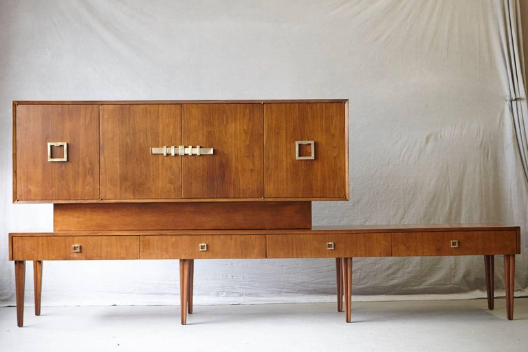 Exceptional long custom-made walnut sideboard or credenza on eight reeded and tapered legs, circa 1940s. Base with four drawers, one silverware drawer with lined felt and felt cover and another drawer also lined with felt. The top has four doors,