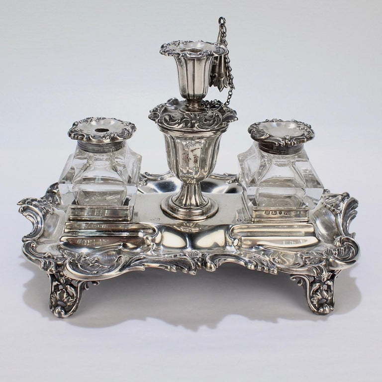 A rare Early Victorian sterling silver inkstand or standish by Henry Wilkinson.  Retaining its original bottles, lids, taper stick, snuffer and a quill or wafer compartment. The body has pierced feet and elaborate swags to the edges and borders