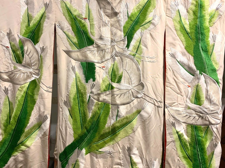 A beautiful vintage Uchikake wedding kimono/robe for ceremonial occasion, circa 1930s-1940s in the Oriental Art Deco style. The bridal garment of a pale white silk features elaborate and intricate embroidery of motifs of flying cranes and large