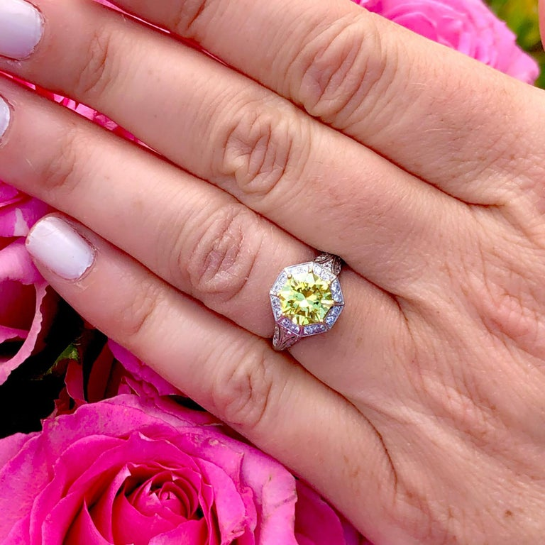 An extraordinary diamond set in an extraordinary custom French ring! This incredible piece showcases an impressive 1.88 carat GIA Fancy Intense Yellow Octagonal Cut Modified Brilliant Diamond set in a vintage inspired platinum mounting by French