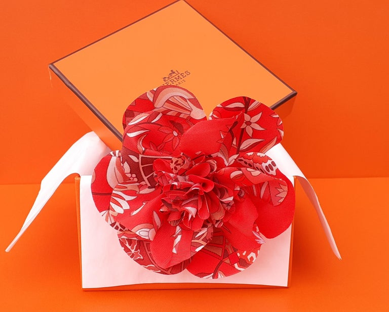 Gorgeous Authentic Hermès Flower  A clip on the back allows it to be worn as a brooch, as a charm, wherever you want  Made in France  Made of 100% Silk  Colorways: Red, White, Salmon Pink, Brown  Measurements: Around 10,5 cm Diameter (4,13