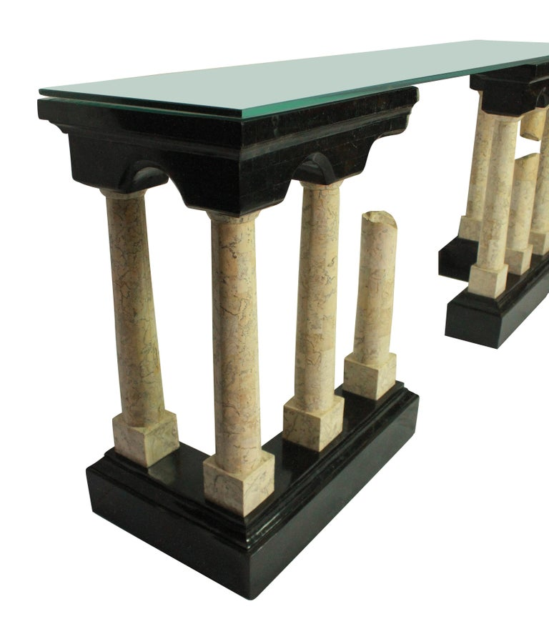 An exceptional Italian console table depicting ancient Roman ruins in polished marble veneers. The base and pediment in a very dark green, with ivory colored pillars. With a plate glass top.