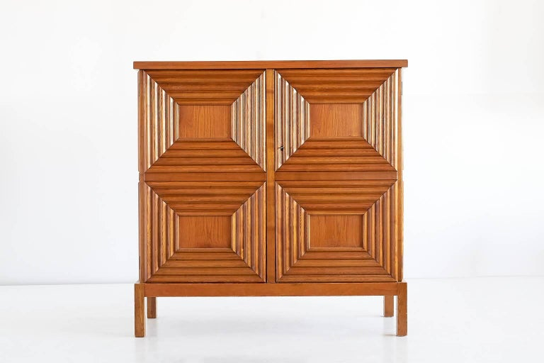 This cabinet designed by Oscar Nilsson and executed by the master cabinetmaker Jacob Wickman was produced in Sweden in the early 1940s. The exterior of the oak cabinet is composed of eight geometrically profiled frames, four on the front and two