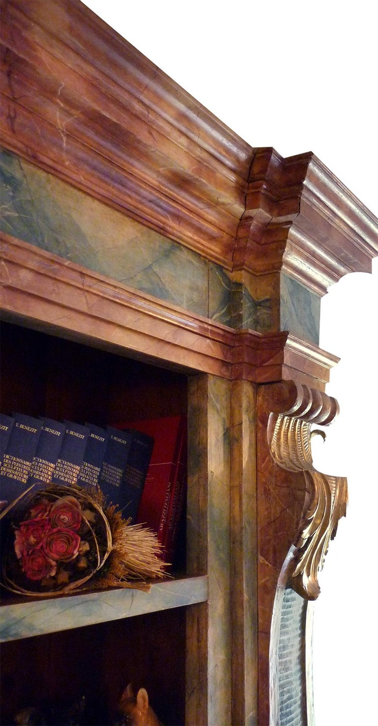 Exceptional bookcase painted in blue and red with gold leaf carvings. Two large side pillars, with richly carved scrolls, lacquered and gilded with gold leaf, on the notches carved and gilded acanthus leaves. Rich upper cornice lacquered with blue