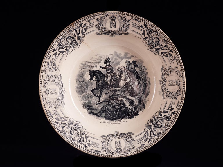 Superbly elegant set of 9 white faïencerie plates from the 1890s depicting major French battle scenes of the late 18th and early 19th century. The items are beautifully painted with stamped black designs based on a
