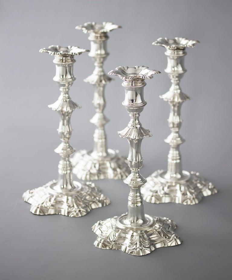 An extremely fine set of cast Silver candlesticks of petal form decoration rising from a stepped, hexagonal rope twist decorated base to a tapered fluted column beneath a hexagonal knop. The capitals of cotton reel form with rope twist decoration.