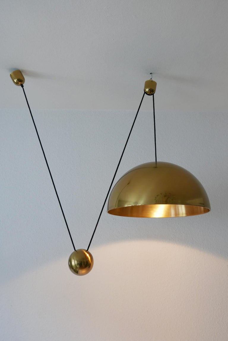 Elegant and extremely rare, large Mid-Century Modern counterweight pendant lamp Solan by Florian Schulz, Germany, 1980s.  Executed in solid polished brass. The lamp needs one E27 Edison screw fit bulb, is wired. It runs both on 110 / 230