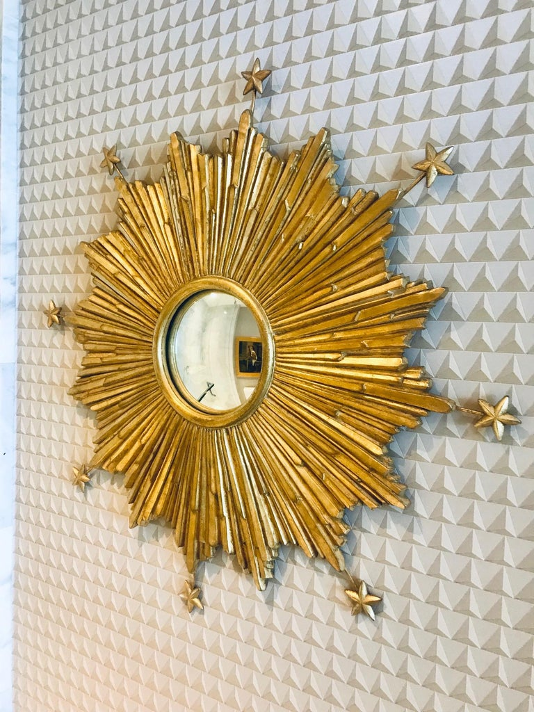 Exquisite sunburst mirror with extended star accents. Hand made by artisans using casting technique of wood, resin, and wire to create three dimensionality form. Features a central convex mirror and hand laid antique gold leaf finish.