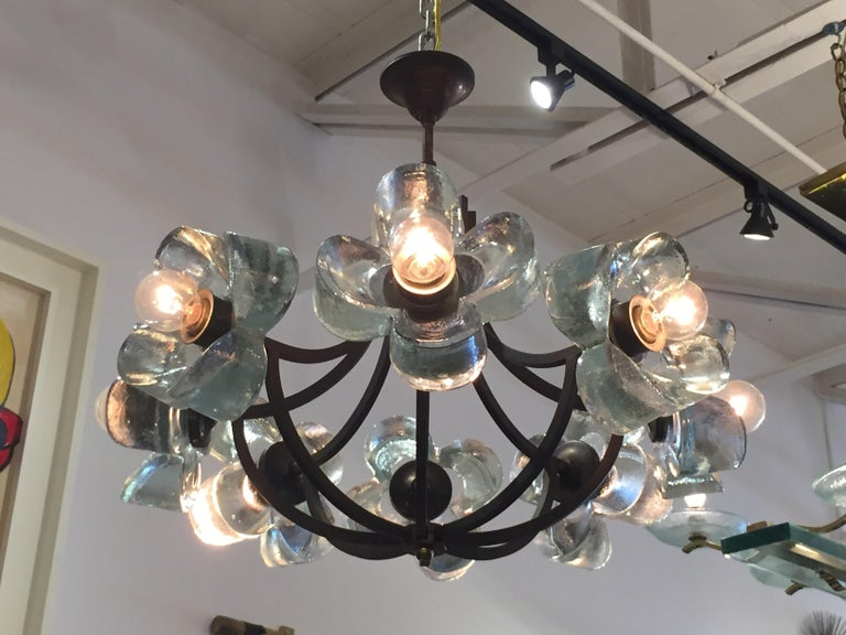 Comprised of 8 molded thick glass daisies, this dark brass framed chandelier is whimsical and unique. All original, as found and working well. E-14 light bulbs (European base and easy to source). The dark brass is patinated by age.