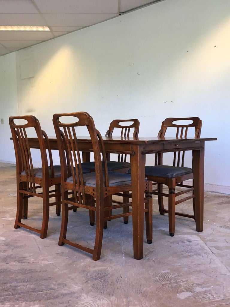 This wonderful dining room set was manufactured by (Frits) Schuitema & Zonen in the Netherlands. It features four exclusive Art Deco style chairs and a dining table with a drawer to the side. All of the pieces are sturdy and in a very nice