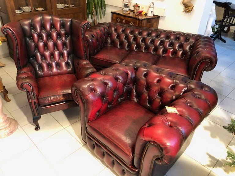 Exclusives comfortable Chesterfield three part living room set. The set consists of one three-seat sofa, one club armchair and one wing chair. Features a Classic Chesterfield club design and an oxblood antique red color. The living room set is