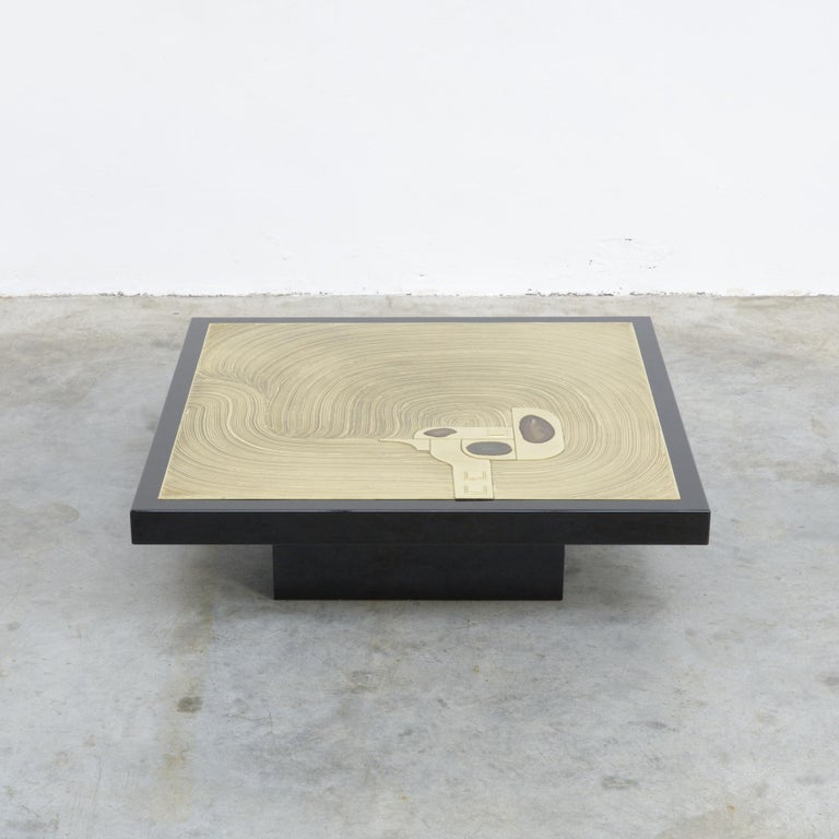 This exclusive coffee table was designed and created in the workshop of Marcel and Jean-Claude Dresse. It can be dated in the 1970s. The table is made of glossy black lacquered resin with a brass inlay. The artist created an amazing design with