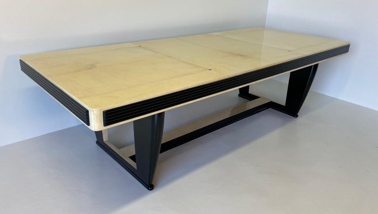 This table was produced in Italy in the 1940s. The top is entirely covered in parchment leather with ebony inlays. The leg and the shape of the top are in black lacquered wood while the central part of the leg is also covered in