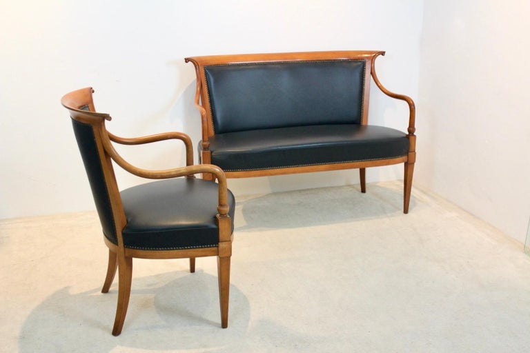 Exclusive and stylish black leather sofa and chair in 'Directoire' style handmade by the Italian company Selva in the 1990s (marked). The frames are made in solid beech and very nicely manufactured. The leather has some normal wear but overall in