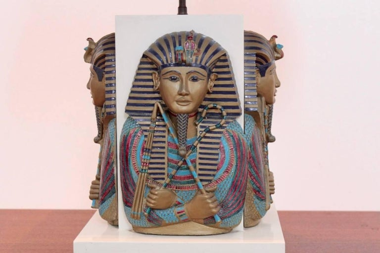 Exclusive, unique and exotic Toetanchamon table lamp from the 1950s and made in France. This luxurious lamp features four Pharaoh masks on each side very detailed and beautiful sculptured and painted in original colors. Very heavy table lamp coming