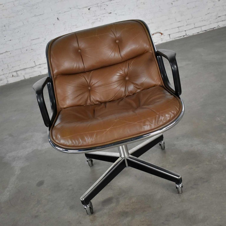 Handsome executive chair by Charles Pollock for Knoll. Comprised of brown leather, aluminum band, chrome shaft, black plastic arms, and a 4-prong stainless base with casters. Wonderful vintage condition with some tightening of the buttons as they